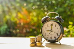 Alarm clock and coins on the wooden table in the sunset, money concept. Alarm clock and money coins stack on wood table and sunset background in the public park royalty free stock image