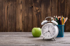Alarm-clock with colored pencils and green apple on wooden table Stock Photography