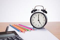 Alarm clock among colored pencils and notebook stock images
