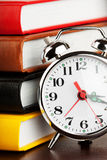 Alarm clock and colourful books. Extreme closeup stock photography