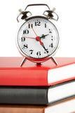 Alarm clock and colourful books Stock Image