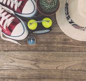 Alarm clock, compass, cactus, sneakers and  straw hat on wooden Royalty Free Stock Photography