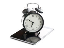 Alarm clock and computer tablet Stock Photography