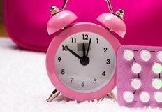 Alarm clock and contraceptive pills Royalty Free Stock Photos