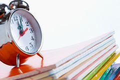 Alarm clock on copybooks Stock Image