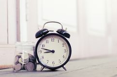 Alarm clock copyspace to the left for text, ideal for concept of measuring passing time, deadlines and time management. Vintage alarm clock copyspace to the left stock photo
