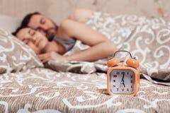 Alarm clock with couple sleeping on background. Stock Photo
