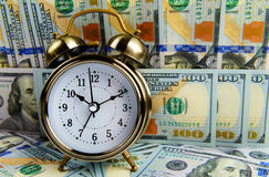 Alarm clock covered pile of money Royalty Free Stock Images