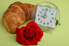 Alarm clock, croissant and rose Stock Images