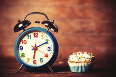 Alarm clock and cupcake. Royalty Free Stock Photo