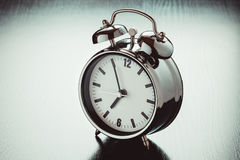 Alarm clock on dark bedside table Royalty Free Stock Photos