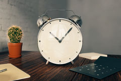 Alarm clock on desk. Glossy alarm clock on wooden desk with cactus, calculator and other items. 3D Rendering Royalty Free Stock Photos