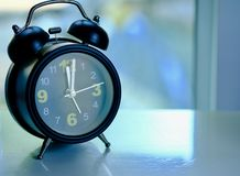 Alarm clock on desk at noon. In office . Lunch time concentrate stock photography