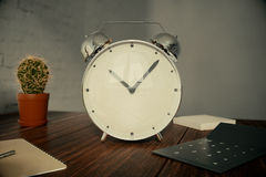 Alarm clock on desktop. Glossy alarm clock on wooden desktop with cactus, calculator and other items on light wall background. 3D Rendering Royalty Free Stock Image