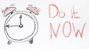 Alarm clock and Do it Now sign. Drawn alarm clock and Do it Now sign Stock Photos
