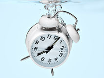 Alarm clock drowning Royalty Free Stock Images