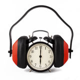 Alarm clock with ear defenders on. Royalty Free Stock Photo
