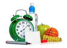 Alarm clock with empty blank. Alarm clock with bottle of water, fresh green apple, measuring tape and empty blank paper card sign for text with red marker Royalty Free Stock Photo