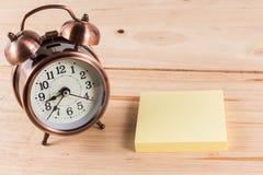 Alarm clock with empty sticky note. Stock Photos