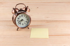 Alarm clock with empty sticky note. Royalty Free Stock Photo