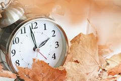 Time Change Daylight Savings Concept. Alarm clock in fallen autumn leaves with shallow depth of field. Daylight savings time concept with clock hands at almost 2 royalty free stock image