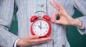 Alarm clock in female hands close up. Teachers attributes. Alarm clock in hands of teacher or educator classroom stock image