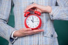 Alarm clock in female hands close up. Teachers attributes. Alarm clock in hands of teacher or educator classroom royalty free stock photography