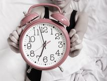 Alarm clock with female hands Stock Photos