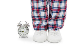 Alarm clock and female legs in pajamas and slippers on a white Stock Image