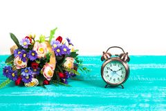 Alarm clock with flower basket on wood. Table Stock Photos