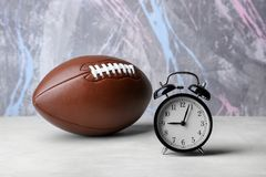 Alarm clock and football ball. On color background Royalty Free Stock Images