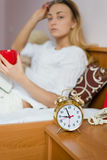 Alarm clock on the foreground and beautiful young blond woman in bed with red cup in her hands looking at camera Stock Image