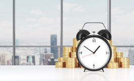 An alarm clock is on the foreground and golden coins which are on the background. Modern New York panoramic office on background. Royalty Free Stock Images