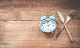 Alarm clock with fork and knife on the table. Time to eat. Royalty Free Stock Image