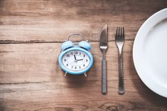Alarm clock with fork and knife on the table. Time to eat. Business concept Royalty Free Stock Images