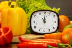 Alarm clock with fresh vegetables for cooking,focus of alarm clock. Alarm clock  fresh vegetables  cooking  alarm clock Stock Photos