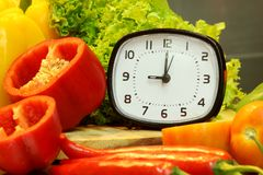 Alarm clock with fresh vegetables for cooking,focus of alarm clock. Alarm clock  fresh vegetables  cooking  alarm clock Royalty Free Stock Image