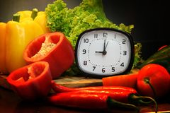 Alarm clock with fresh vegetables for cooking,focus of alarm clock. Alarm clock  fresh vegetables  cooking  alarm clock Stock Images