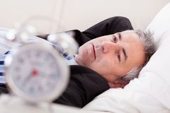 Alarm Clock In Front Of Man Sleeping. Close-up Of Alarm Clock In Front Of Man Sleeping Stock Photos