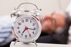 Alarm clock in front of man sleeping. Close-up Of Alarm Clock In Front Of Man Sleeping Stock Photo