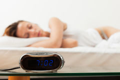 Alarm clock in front of sleeping woman. In bad Royalty Free Stock Photo