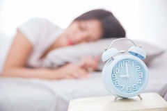 Alarm clock in front woman sleeping on a bed. Alarm clock close up with woman sleeping peacefully on a bed on the back Stock Photography