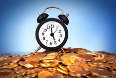Alarm clock with golden coins Royalty Free Stock Photos