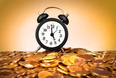 Alarm clock with golden coins Stock Image