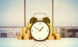 An alarm clock and golden coins are on the table in a modern panoramic office in New York city Royalty Free Stock Image