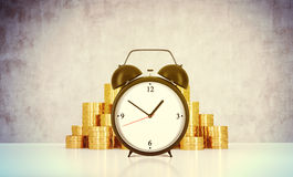 An alarm clock and golden coins are on the table in a room with concrete wall. A concept of time management or billing the service Royalty Free Stock Photography