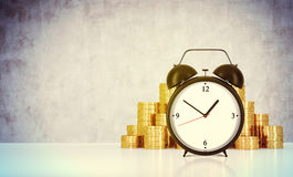 An alarm clock and golden coins are on the table in a room with concrete wall. A concept of time management or billing the service Royalty Free Stock Photos