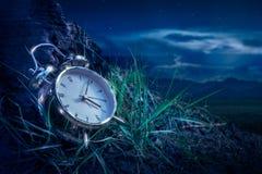 Alarm clock on grass at night Royalty Free Stock Image