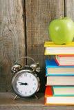 Alarm clock, green apple and books. Stock Image