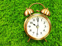 Alarm clock on green grass background Stock Photography